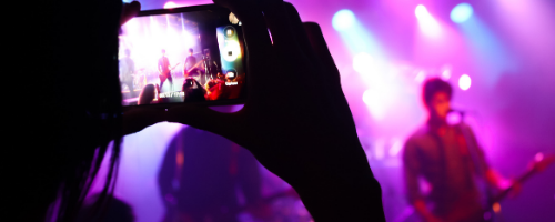 Person takes photo at live music concert