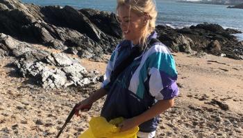 Young women picks litter from beach