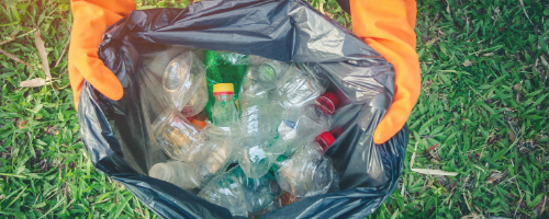 Person holds rubbish bag of plastic bottles